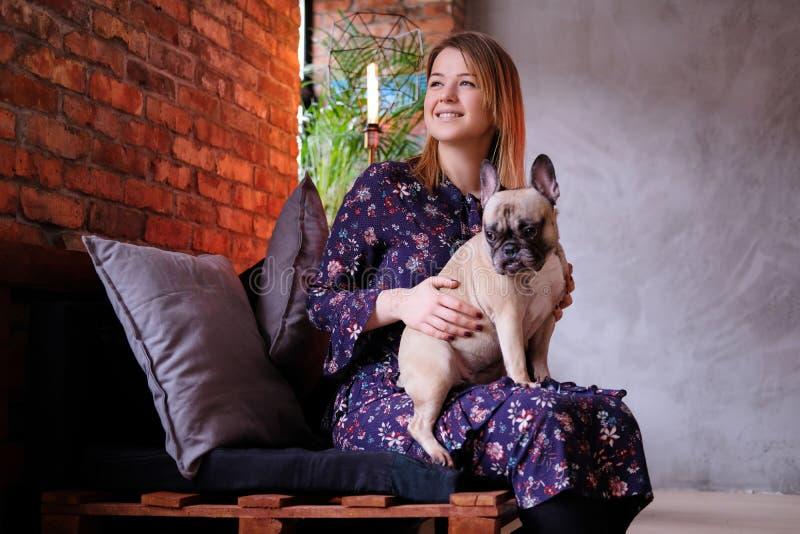 礼服的愉快的白肤金发的妇女与她逗人喜爱的哈巴狗坐一个手工制造沙发在有顶楼内部的屋子里 库存照片
