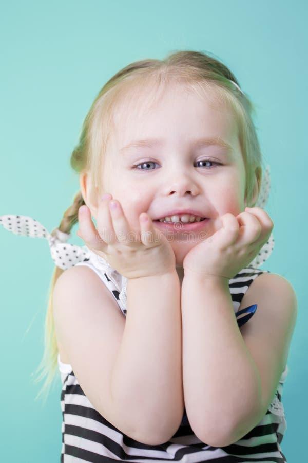 礼服的愉快的矮小的微笑的女孩 库存照片