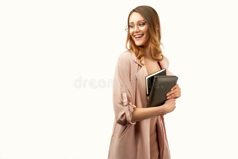 礼服的时髦的女实业家温暖地微笑和抓住笔记本的 免版税库存照片