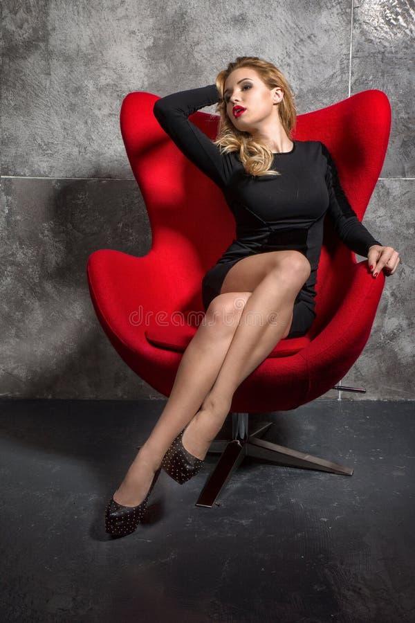 黑礼服的白肤金发的女孩坐红色扶手椅子 免版税库存照片