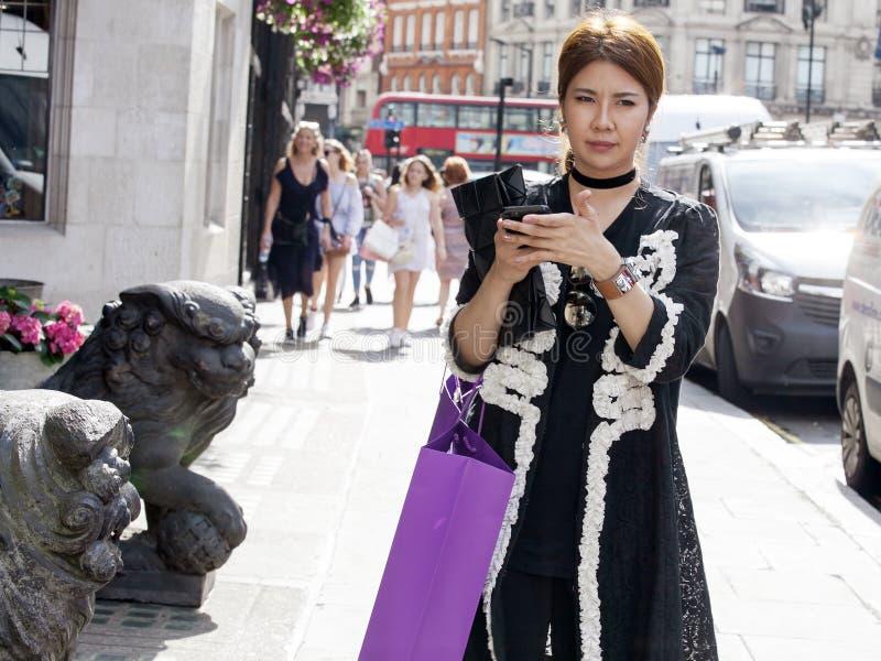 黑礼服的美丽的严肃的亚裔女孩在利物浦街道附近穿过路 免版税库存图片