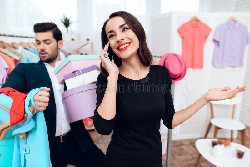 礼服的美丽的女孩和衣服的一个可爱的人购物 他们在一个轻的陈列室里 库存图片