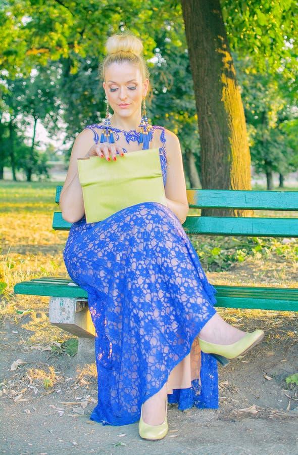 礼服的美丽的女孩坐长凳 免版税库存照片