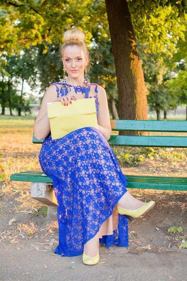 礼服的美丽的女孩坐长凳 免版税库存图片