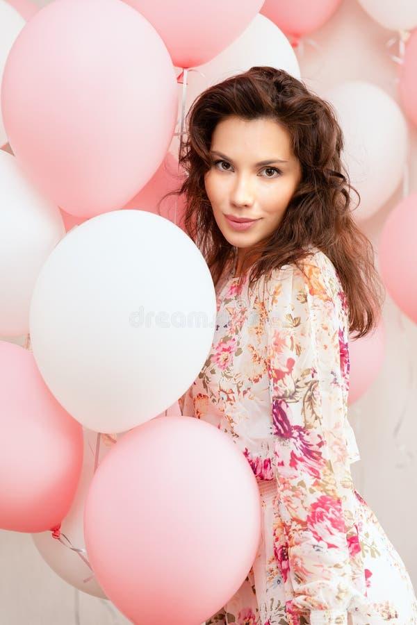 礼服的美丽的女孩有气球的在生日 逗人喜爱的妇女画象有多彩多姿的气球的 逗人喜爱的浅黑肤色的男人 免版税库存图片