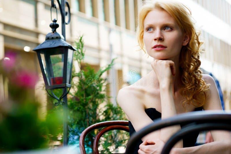 黑礼服的美丽的妇女在咖啡馆在夏日 免版税库存照片