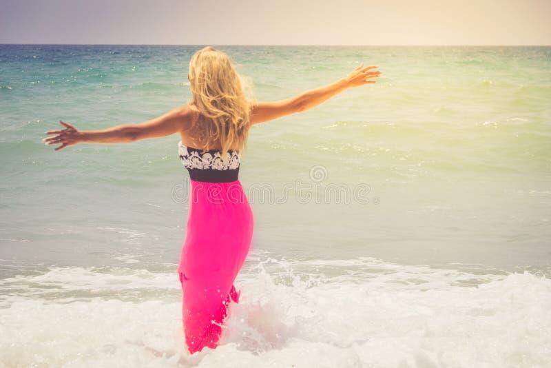 礼服的美丽的妇女走在海滩的 呼吸新鲜空气,在海附近的情感肉欲的妇女的轻松的妇女,享受s 免版税库存图片