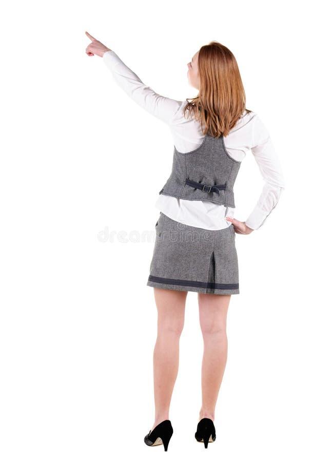 礼服的美丽的少妇指向墙壁的 查出的背面图白色 免版税库存图片