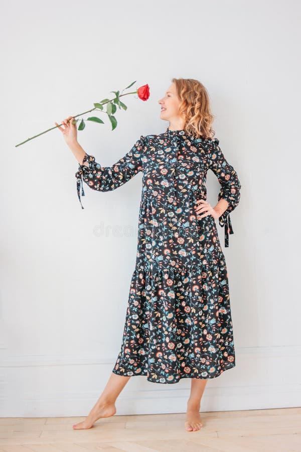 礼服的美丽的浪漫年轻白肤金发的妇女有在白色walll背景,全长画象的红色玫瑰的 免版税库存图片