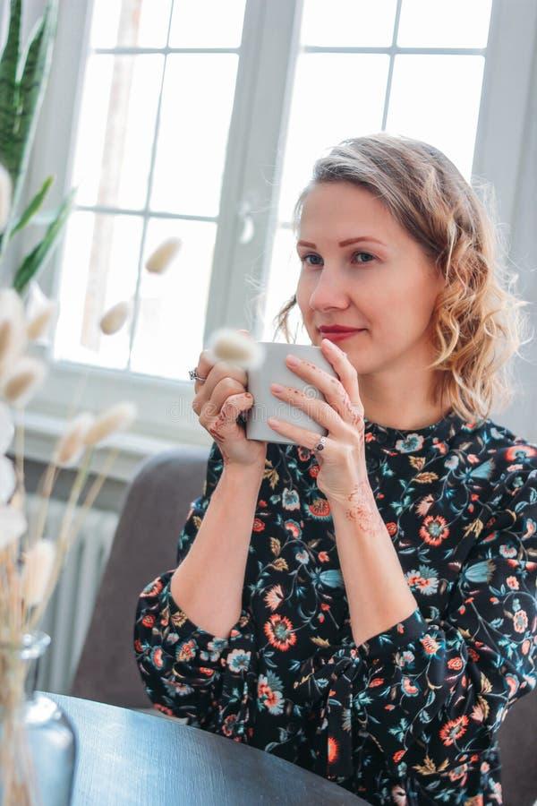 礼服的美丽的浪漫年轻白肤金发的妇女有坐由窗口的茶的 女性首饰,mehendi 库存图片