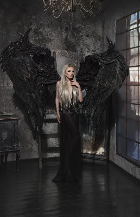 黑礼服的美丽的白肤金发的妇女有翼的 免版税库存图片
