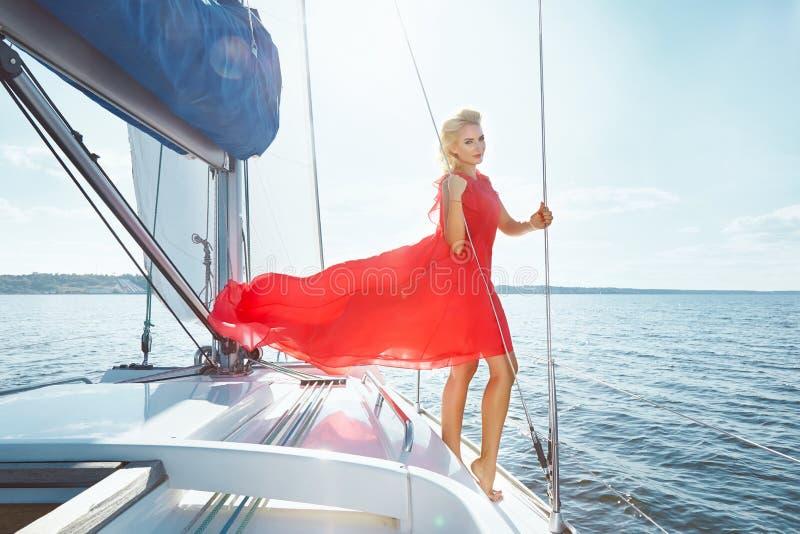 礼服的美丽的年轻性感的深色的女孩和构成、夏天旅行在一条游艇有白色风帆的在海或海洋海湾的 库存照片