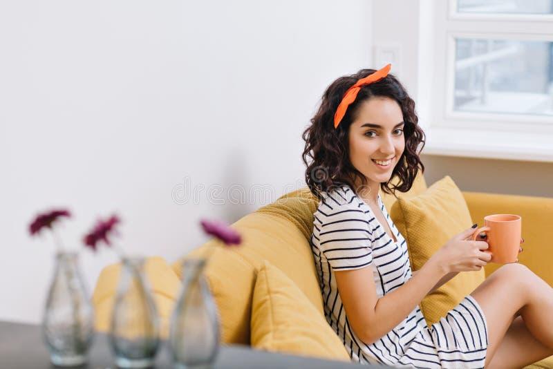 礼服的迷人的年轻女人微笑对在长沙发的照相机的在现代公寓 橙色,白色,金黄颜色,快乐 库存照片