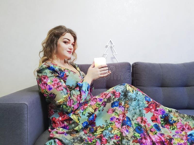礼服的,卷发,坐的蜡烛,典雅的长沙发秀丽女孩 免版税库存照片