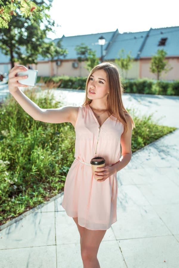 礼服的,夏天女孩在城市,在电话,在智能手机的照片selfie,应用在她的手上站立,在网上社会 库存图片
