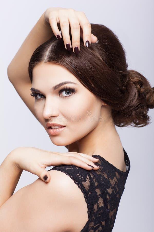 黑礼服的年轻美丽的深色的妇女 免版税库存图片