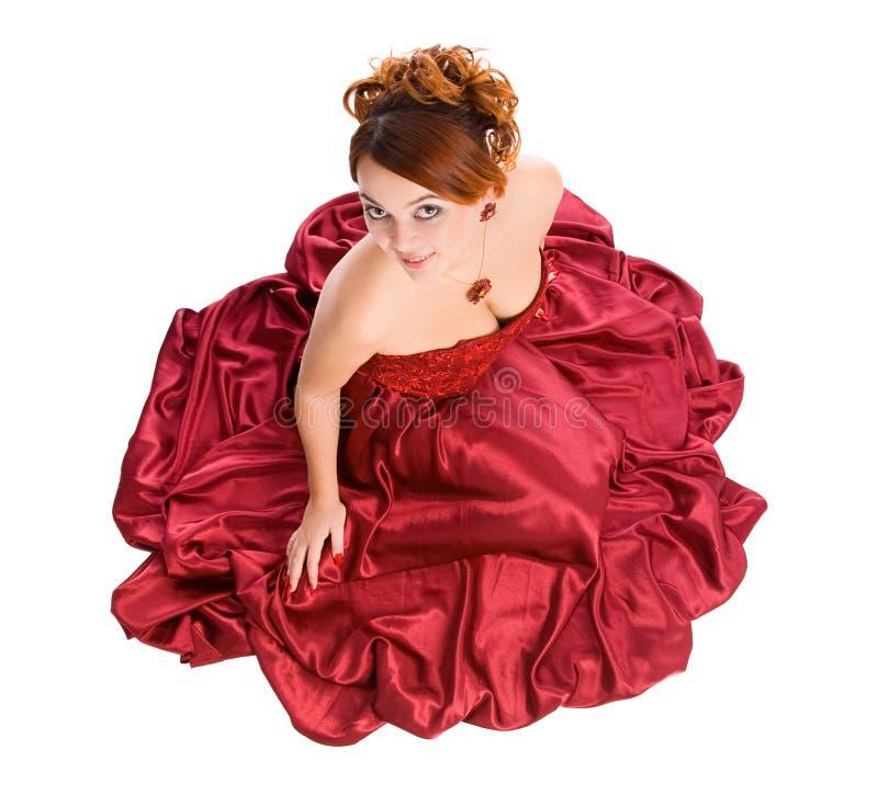 礼服红色坐的妇女 图库摄影