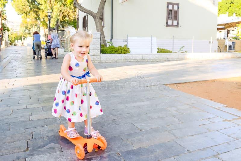 礼服骑马滑行车的逗人喜爱的矮小的情感blondy小孩女孩在与大厦和树的城市公园度假区 Activ 免版税库存照片