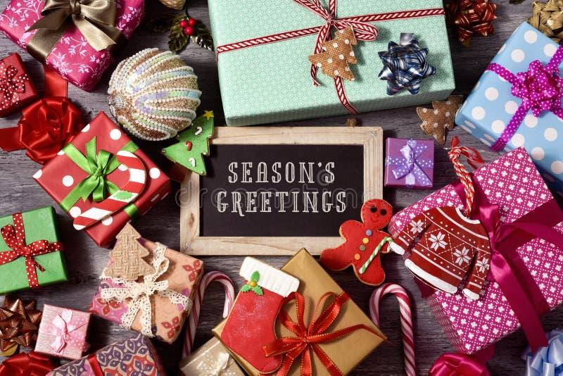 礼物、圣诞节装饰品和文本季节问候 库存图片