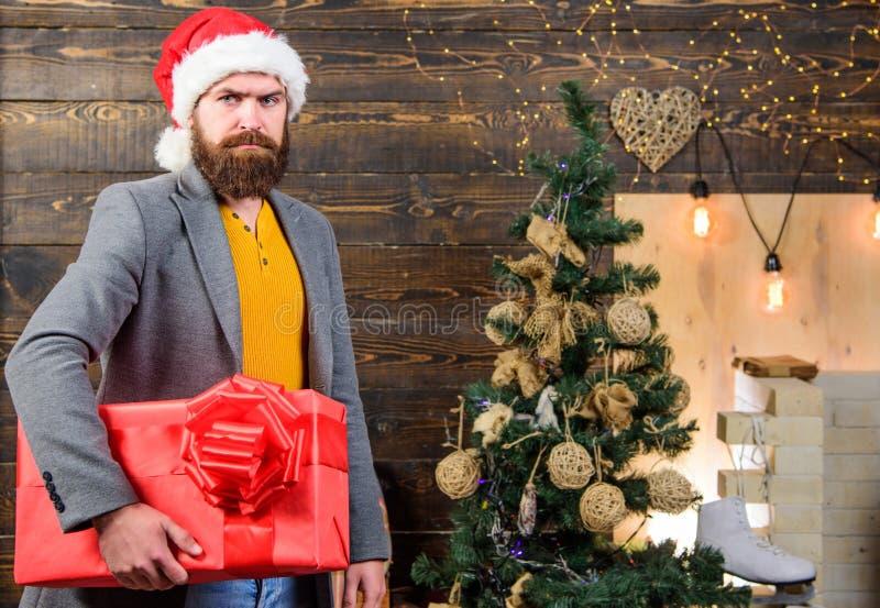 礼物交付 人圣诞老人帽子交付礼物 被传播的幸福和喜悦 有胡子的人严肃的面孔运载当前箱子 库存图片