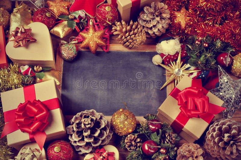 礼物和圣诞节装饰品和一个空白的黑板 免版税库存图片