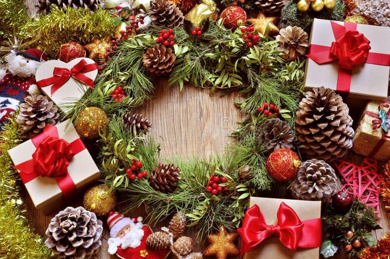 礼物和圣诞节装饰品在一张土气木桌上 库存图片