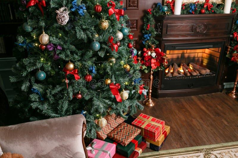 礼物和礼物盒在圣诞树下 有丝带弓的五颜六色的箱子 新年装饰了房子内部 冬天 库存图片