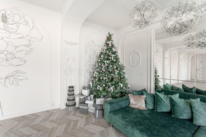 礼物和礼物盒在圣诞树下 有丝带弓的米黄箱子 新年装饰了房子内部 冬天 免版税库存照片