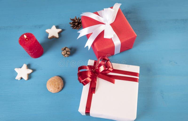 礼物和被点燃的蜡烛在木桌上 库存图片