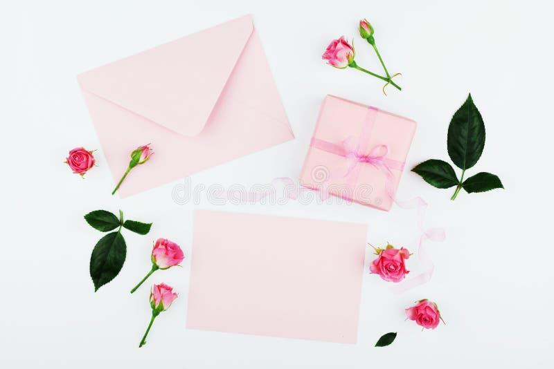 礼物或当前箱子、信封,纸空白和桃红色玫瑰色花在白色台式视图在舱内甲板放置样式贺卡的 图库摄影