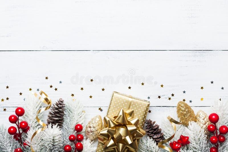 礼物或当前箱子、多雪的杉树和圣诞节装饰在白色木台式视图 平的位置 库存图片