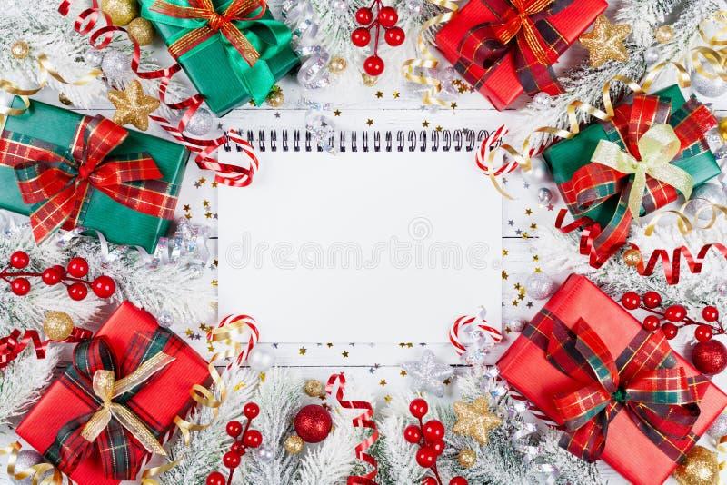 礼物或当前箱子、空的笔记本、多雪的杉树和圣诞装饰在白色木台式视图 平的位置 计划 免版税库存照片
