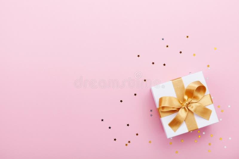 礼物或当前箱子和星五彩纸屑在桃红色台式视图 生日、母亲节或者婚礼的平的位置构成 免版税图库摄影