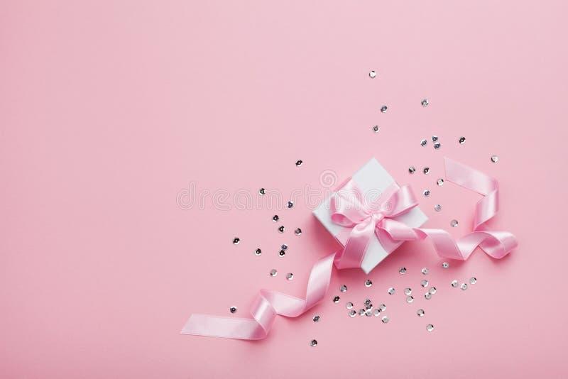 礼物或当前箱子和衣服饰物之小金属片在桃红色台式视图 平的位置 生日、婚礼或者圣诞节概念 免版税库存照片