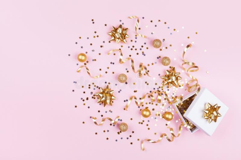 礼物或当前箱子有五彩纸屑星、金黄丝带和假日装饰的在桃红色背景 圣诞节模式 平的位置 免版税库存图片