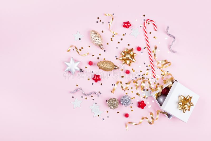 礼物或当前箱子有五彩纸屑星、金黄丝带和假日装饰的在粉红彩笔背景 圣诞节舱内甲板位置 库存图片