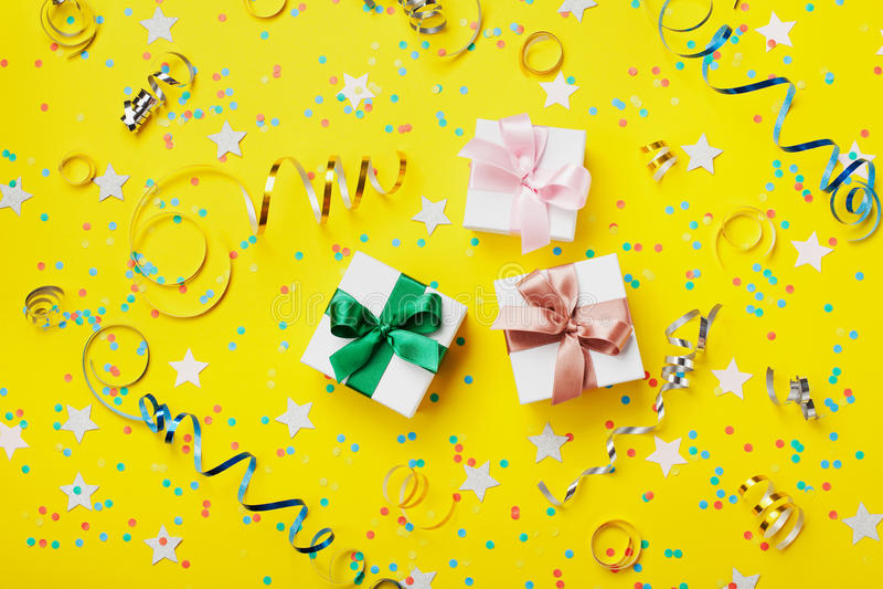 礼物或当前箱子装饰了五颜六色的五彩纸屑、星、糖果和飘带在黄色台式视图 平的位置样式 生日 免版税库存图片