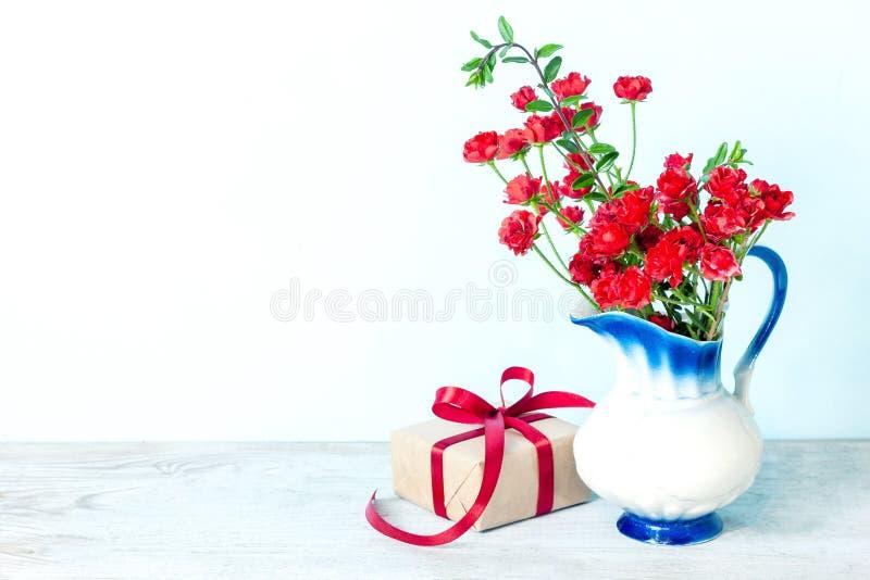 礼物或礼物盒在一张工艺纸与红色丝带弓在白色背景 免版税库存图片