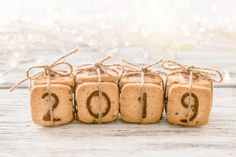 礼物欢乐圣诞节数字2019由曲奇饼做了在与光和bokeh的白色背景 可口面包店甜点confectione 免版税图库摄影