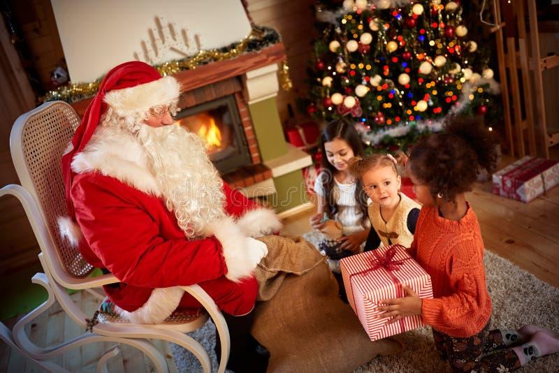 给礼物的圣诞老人在h前面的一个小逗人喜爱的女孩 免版税库存照片