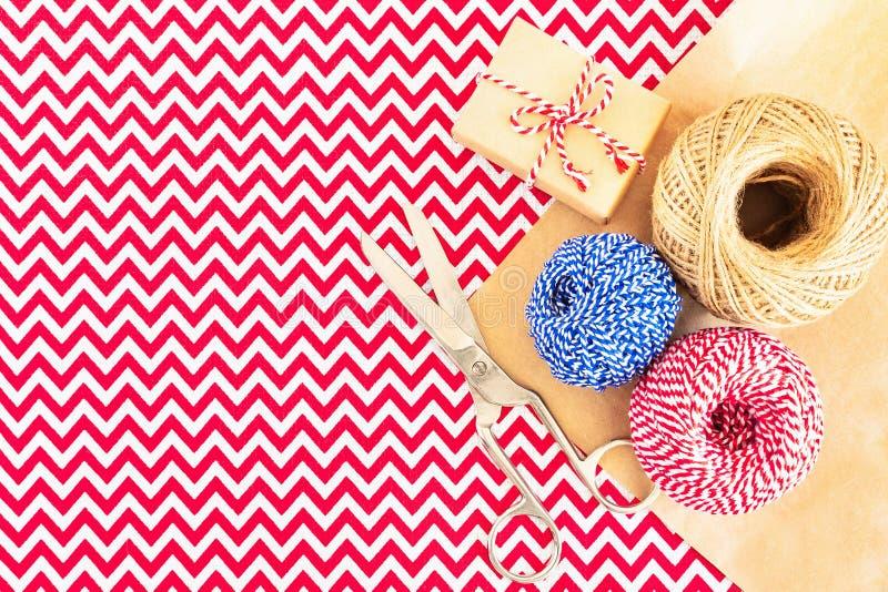 礼物盒、卷串,卡拉服特包装纸和剪刀圣诞节平位置在红色与白色织品桌布 图库摄影