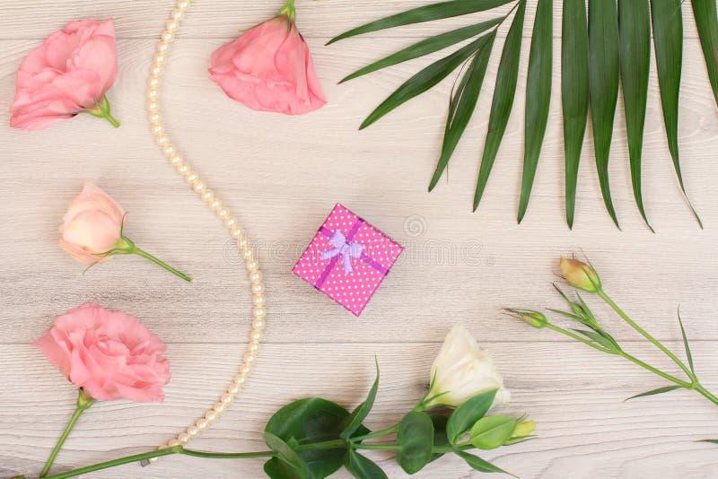 礼物盒、小珠与花和叶子在木板 库存图片