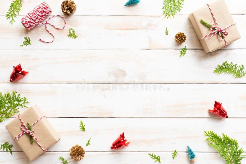 礼物盒、杉木锥体、红色星和响铃顶视图在木白色背景 免版税库存照片