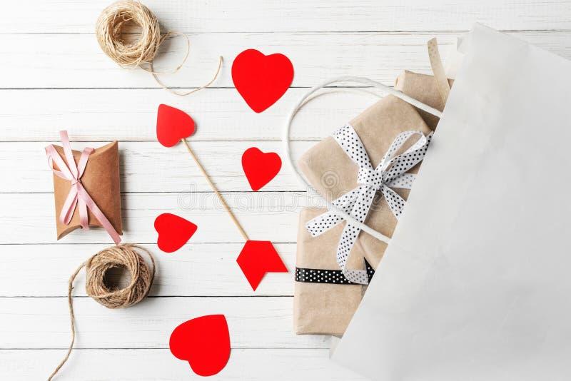 礼物盒、纸裁减心脏和购物带来在白色木背景 华伦泰` s日装饰 免版税库存照片
