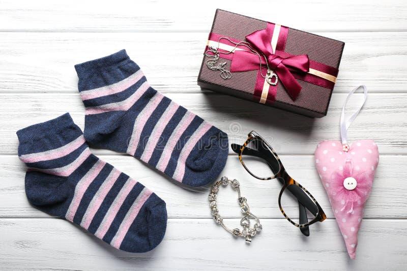 礼物盒、首饰辅助部件,袜子和其他在木backgro 免版税库存图片