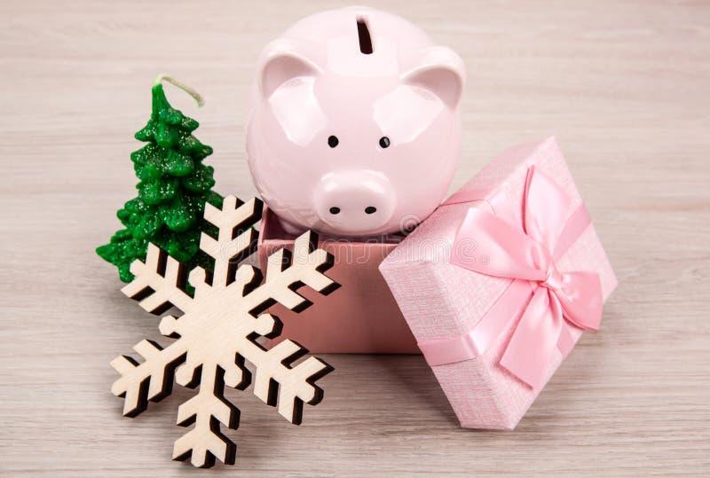 礼物盒和新年的属性的桃红色存钱罐 免版税库存图片