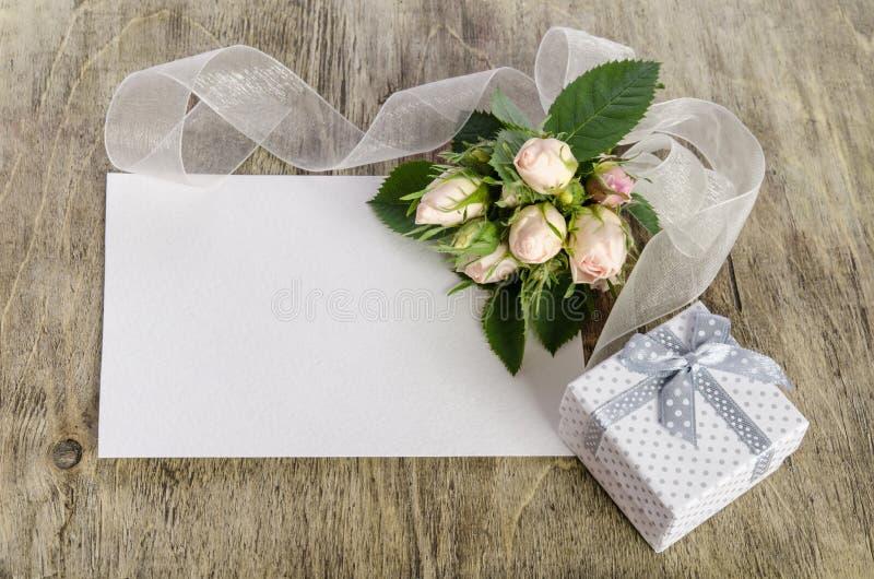 礼物盒和白玫瑰与空的卡片 免版税库存图片