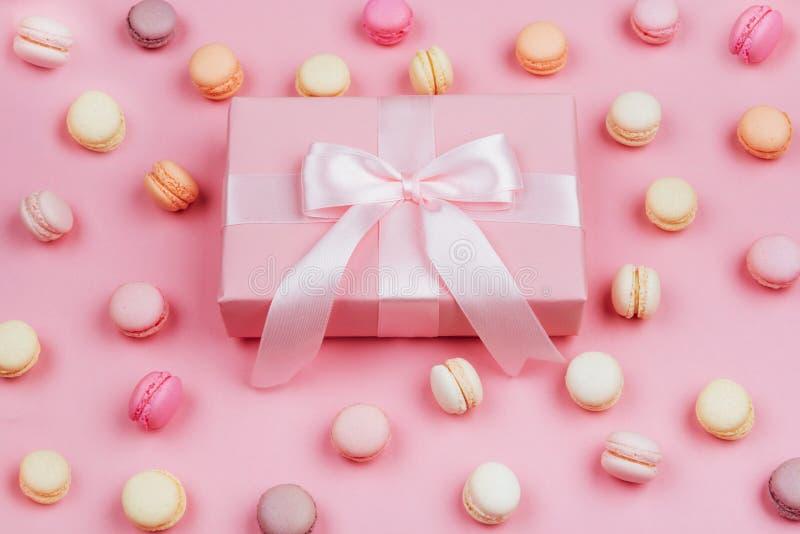 礼物盒和macarons在桃红色背景 免版税库存图片
