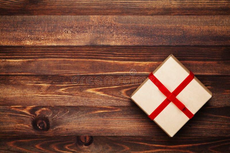 礼物盒圣诞节背景有红色弓丝带的在土气木台式视图 平的位置 库存图片
