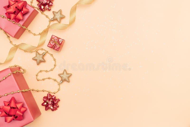 礼物盒或提出有红色弓、星和球的箱子在生日、圣诞节或者婚礼的金黄背景 库存图片